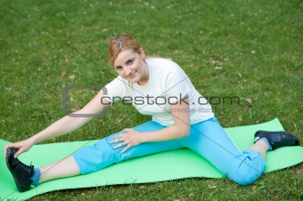 Attractive young woman stretches muscles in park