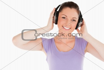 Cute woman posing with headphones while standing