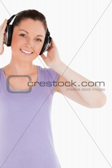 Attractive female posing with headphones while standing