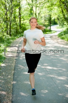 Attractive young woman on a run in nature