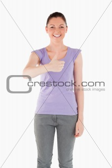 Beautiful woman posing with her thumb up while standing