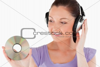 Beautiful woman with headphones holding a CD while standing