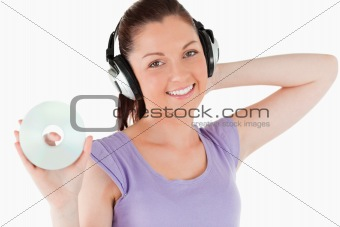 Charming woman with headphones holding a CD while standing
