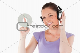 Cute woman with headphones holding a CD while standing