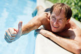 Young man showing  a thumbs up near swimmingpool