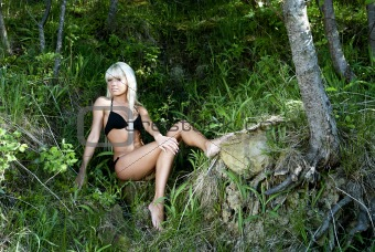 blonde girl in a black bathing suit sitting in the forest