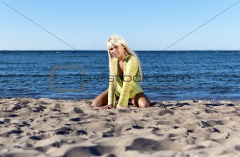 blonde girl in a yellow tunic, sits near the sea on his knees
