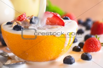 Pouring Milk Over Wholewheat Cereal with Fresh Fruits