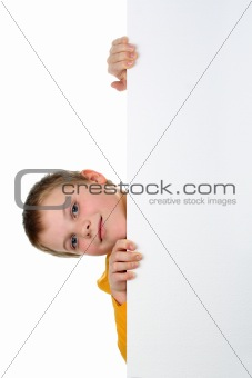 Small boy looks out of blank billboard with his head tilted to the side isolated on white