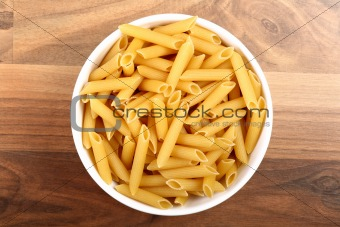 Top view of dry penne rigate in white ceramic bowl on wooden floor