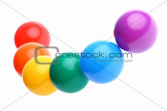 Six shiny coloured plastic toy balls in row isolated on white. Copy space and room for text available