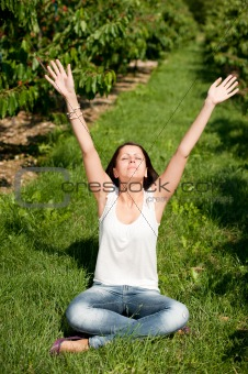 Cute young girl sitting on ground with hands up at cherry plantation