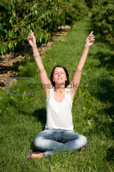 Cute young girl sitting on ground with hands up at cherry planta