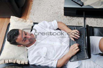 Portrait of a relaxed young guy using laptop at home