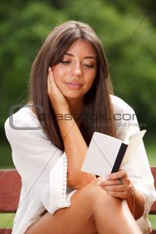 Beautiful woman reading small book