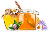 sweet honey in glass jars with spoon and flowers