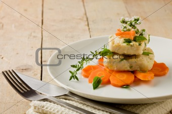 Cod on carrot bed with fresh oregano and basil