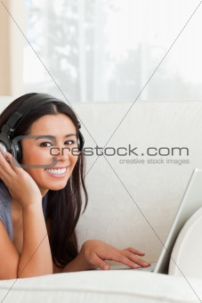 charming woman with earphones lying on sofa smiling into camera