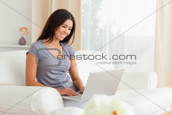 cute woman sitting on sofa with notebook
