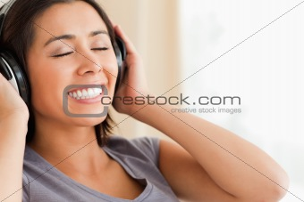 close up of smiling woman sitting on sofa with earphones and eye