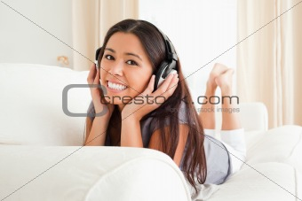 charming woman lying on sofa with earphones looking into camera