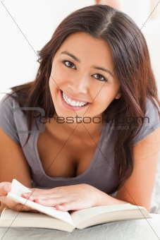 close up of a cute woman holding a book in her hand ans looking