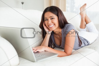 cute woman lying on sofa with notebook smiling into camera