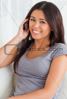 close up of a phoning woman on sofa looking into camera