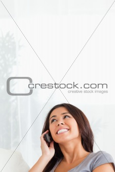 charming woman with mobile looking at the ceiling