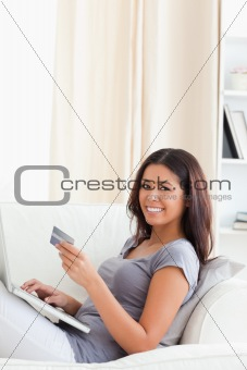 cute woman holding creditcard smiles into camera