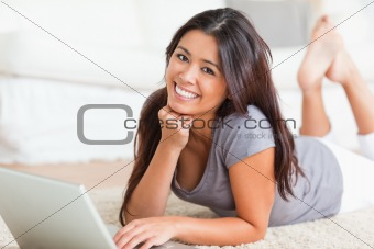 close up of a smiling woman lying on a carpet with notebook look