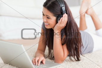 close up of a cute woman lying on a carpet with laptop and earph