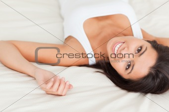 close up of a brunette smiling woman lying on bed