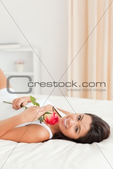 charming woman with rose lying on bed looking into camera