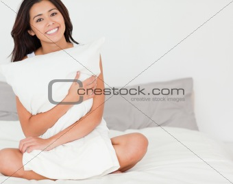 charming woman with pillow sitting on her bed looking into camer