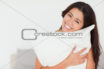 close up of a charming woman with pillow sitting on her bed look