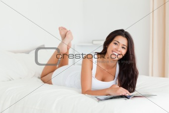 charming woman lying on bed holding a book looking into camera