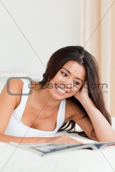 close up of a smiling woman lying on bed reading a magazine