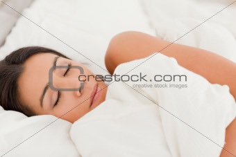 sleeping brunette woman lying under sheet