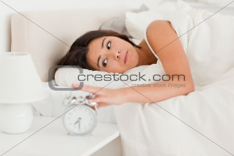 close up of a  cute woman waking under sheet turning off alarm c