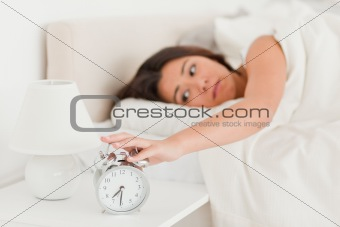 cute woman waking under sheet turning off alarm clock