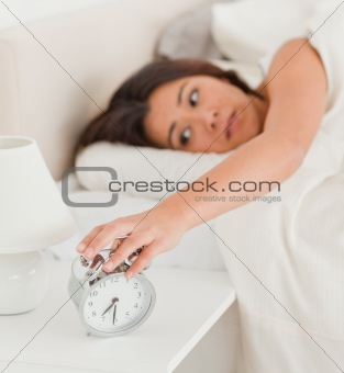 charming woman waking under sheet turning off alarm clock