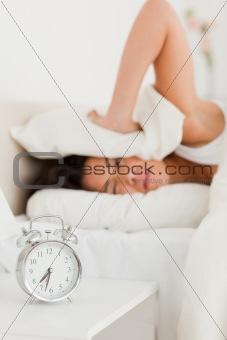 cute woman waking under sheet not wanting to hear alarm clock