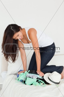 brunette woman kneeing on suitcase trying to close it