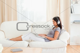 charming woman with earphones sitting on sofa