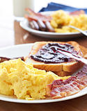 breakfast with scrambled eggs and bacon with toast with jam.