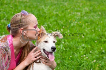 girl kissing puppy