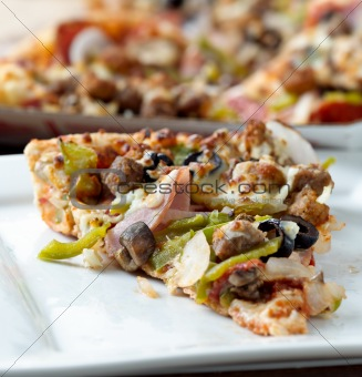 slice of pizza with supreme toppings on a plate