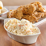 coleslaw with fried chicken in background.