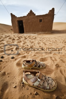 Sandals and house in Sahara desert.